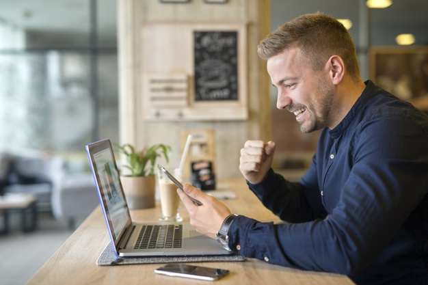 happy-freelancer-with-tablet-laptop-computer-coffee-shop_342744-942